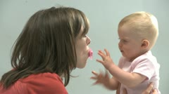 Mother and baby daughter playing with a pacifier Stock Footage