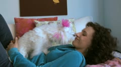 Woman lying on her bed while her white dog licks her face Stock Footage