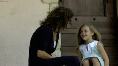 Mother and daughter sitting on a doorstep Stock Footage