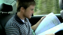 Man looking at a map in the back seat of a car on a road trip Stock Footage