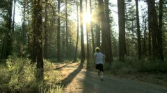 Man running down an isolated country road through a grove of trees Stock Footage