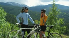 Two cyclists at rest with one of them talking on a cell phone Stock Footage