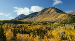 Time lapse movie of clouds moving past mountains covered with fall colors Stock Footage