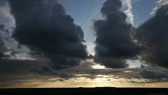 Rain clouds at sunset darken and develop towards the camera Stock Footage