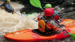 Man and woman in kayaks playing in white water Stock Footage