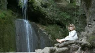 Little girl sitting next to a waterfall Stock Footage