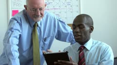 Business men meeting and looking at tablet Stock Footage