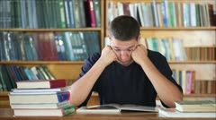 tired student in the library reading books 3 - stock footage