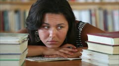 Tired beautiful girl student in the library Stock Footage