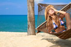 attractive woman relaxing in a hammock - stock photo