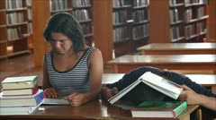 Tired students in the library reading books 2 Stock Footage