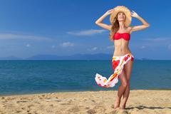 Girl wearing bikini and hat, posing at the beach Stock Photos