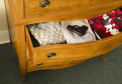 open dresser drawer with gun - stock photo