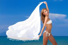 Attractive woman in white bikini holding scarf Stock Photos