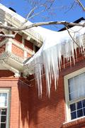 A Build Up Of  Icicles On An Old Houses Roof - stock photo