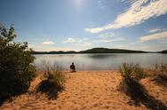 Stock Photo of alone on the beach of a calm wilderness lake