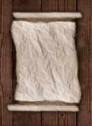 worn parchment paper on a wooden rustic background - stock illustration