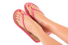 Female legs with flip-flops, isolated on white background. Stock Photos