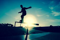 skateboarder silhouette on a grind - stock photo
