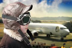 boy playing with pilot´s hat and airport background - stock photo