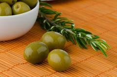 green olives in a white ceramic bowl - stock photo