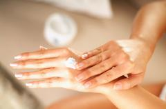 Young women applying cream on her skin  Stock Photos