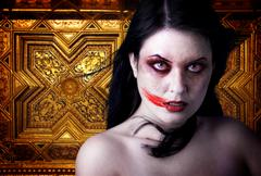 woman vampire with blood in his mouth. gothic image halloween over gold backg - stock photo