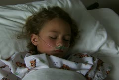 Child with respirator in hospital bed sleeping - stock footage