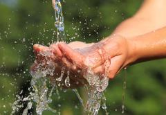 Woman's hands with water splash Stock Photos
