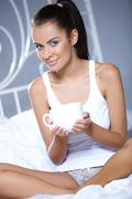 Beautiful woman is resting on white bed Stock Photos