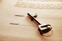key lying on a lease document - stock photo