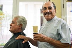 portrait of senior man working as barber in hair salon - stock photo