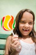 Portrait of pretty female child with lollipop smiling Stock Photos
