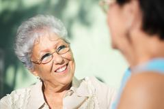 Old friends, two happy senior women talking in park Stock Photos