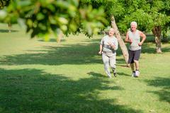 Active senior people jogging in city park Stock Photos