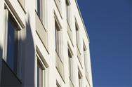 Stock Photo of Detail of white building facade against clear blue sky.