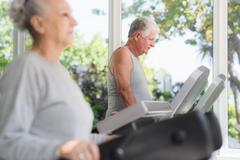 Stock Photo of senior man exercising in wellness club