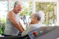 Active senior friends talking and working out in fitness club Stock Photos