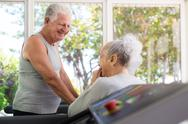 Stock Photo of active senior friends talking and working out in fitness club