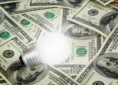 lamp on dollars background - stock photo