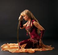 beauty arabian dancer sit with saber - stock photo
