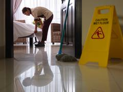 maid at work and cleaning in luxury hotel room - stock photo