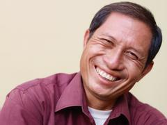 Happy mature asian man smiling and looking at camera Stock Photos