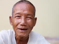 portrait of happy old asian man smiling at camera - stock photo