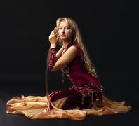 beauty woman in arabian costume sit with saber - stock photo