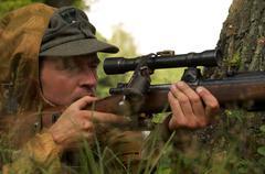 Man in form of nazi sniper aims near a tree Stock Photos
