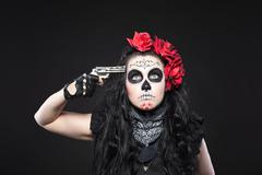 serious woman in skull mask shot in head - stock photo