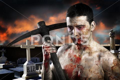 Stock photo of male zombie in a cemetery, undertaker with pick axe