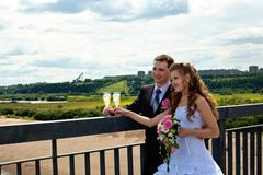 wedding couple in sunny summer day stand on bridge - stock photo