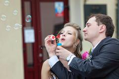 Just married couple blow bubbles Stock Photos